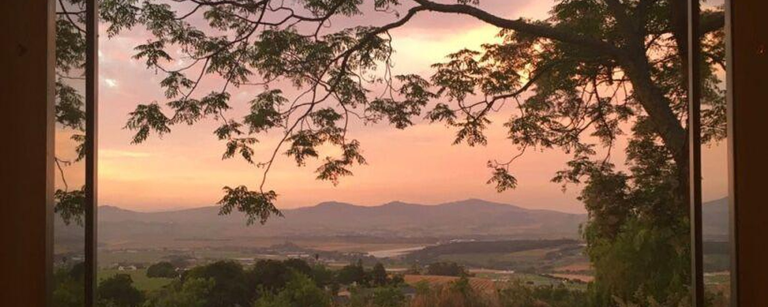A sunset view over farmlands towards Stellenbosch hills and Table Mountain